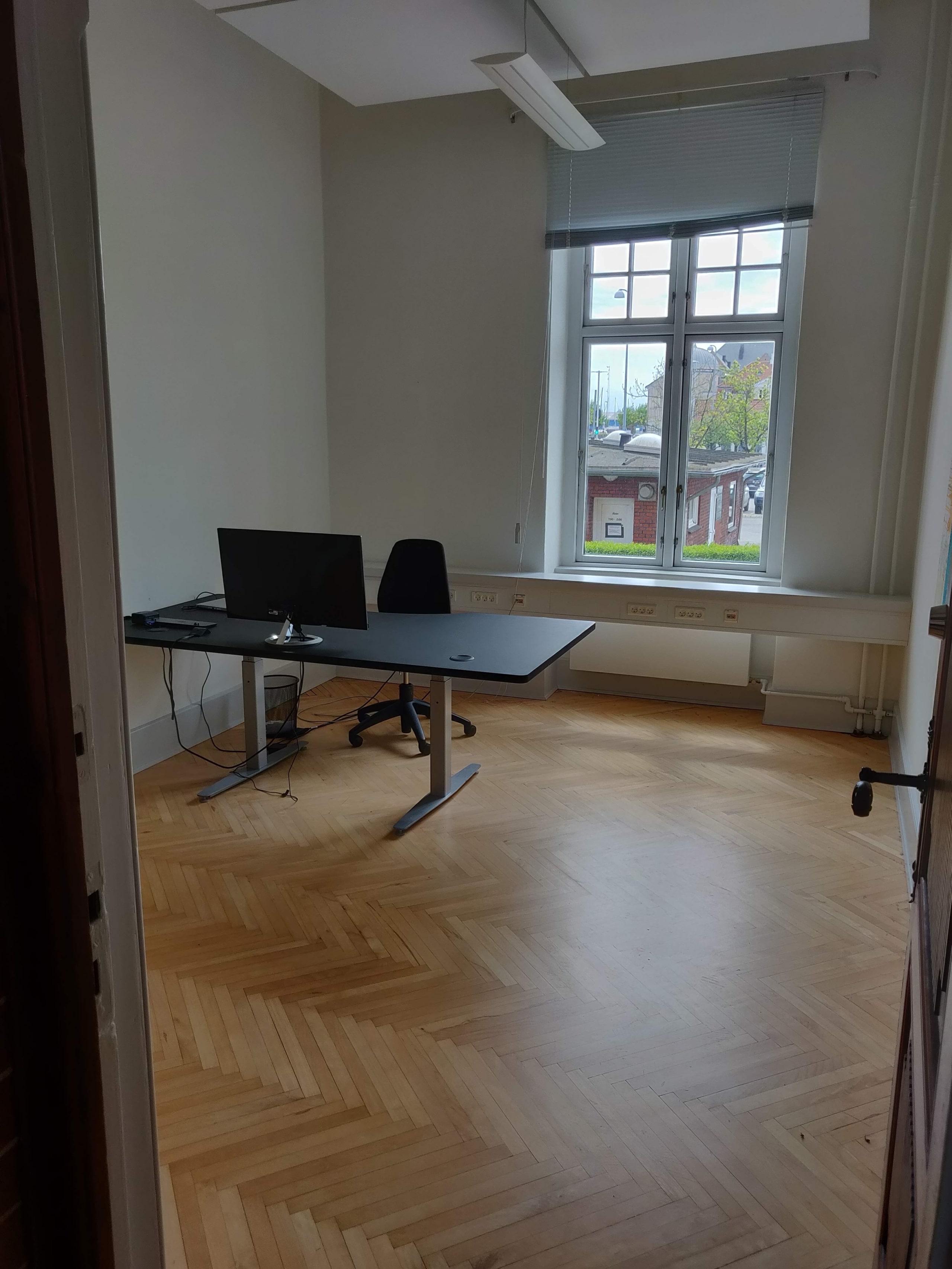 Et lukket kontor, med et flot sildebensparket, samt kontormøbler. Du kan leje det hos os.